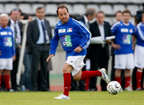 French Socialist Party first secretary Hollande chases ball during charity soccer match in Paris
